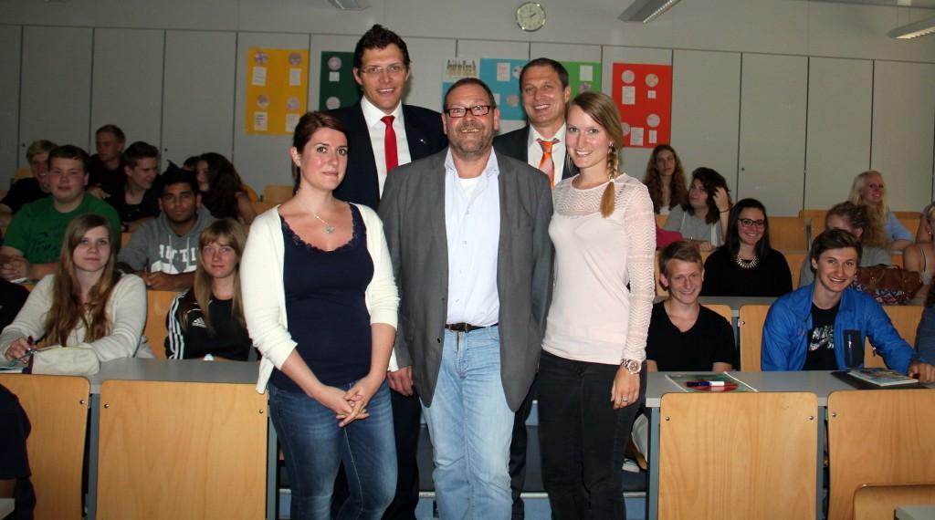 Auf dem Foto sehen Sie: Jürgen Wöllmer von der Fachakademie Hensoltshöhe mit zwei seiner Studentinnen, Walter Niederlöhner Raiffeisenbank) und Stefan Meier (Wirtschaftsjunioren); im Hintergrund ein Teil der Schüler der 11. Klassen